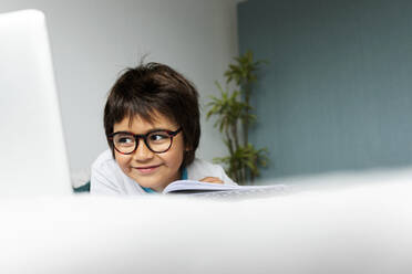 Portrait of relaxed little boy lying on bed using laptop for doing homework - VABF02773