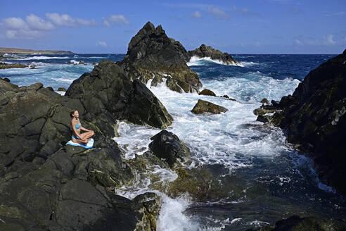 Woman meditating at natural pool, Arikok National Park, Aruba, Antilles - ECPF00886