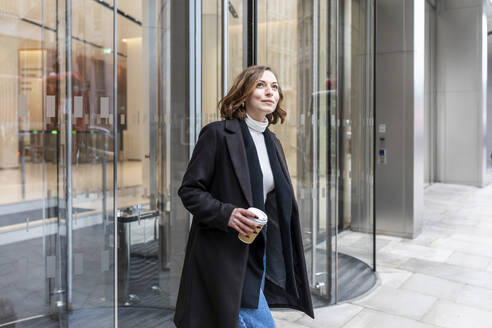Woman in the city coming out from revolving door, London, UK - WPEF02764
