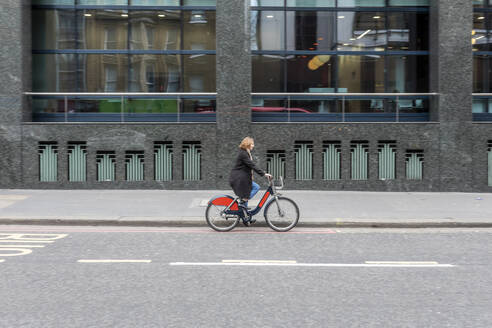 Woman riding bicycle in the city, London, UK - WPEF02767