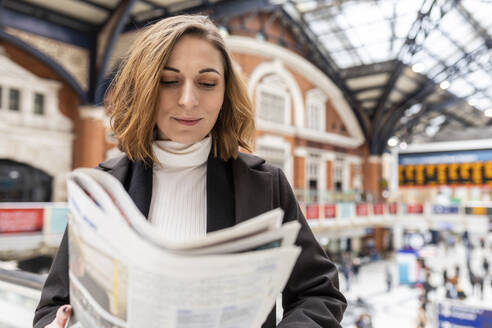 Woman at train station reading a newspaper, London, UK - WPEF02773
