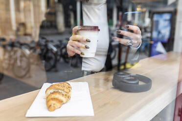 Close-up of businesswoman having a coffee break and using mobile phone at a cafe in the city - WPEF02779