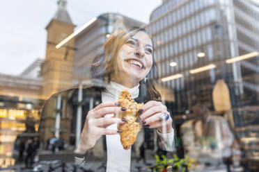 Happy businesswoman having a snack at a cafe in the city - WPEF02782