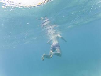 Man floating in water, underwater view - WPEF02805