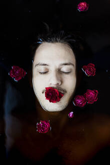 Portrait of young man with red rose in his mouth floating in water - GMLF00013