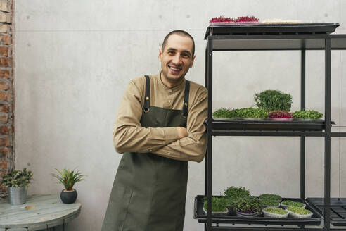 Portrait of happy man leaning against shelf with microgreens - VPIF02273