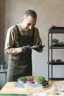 Happy man taking smartphone picture of microgreens on table - VPIF02276