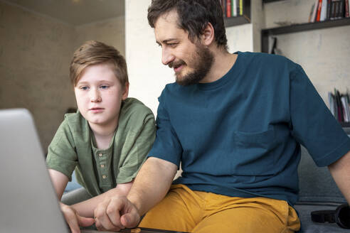 Portrait of father and son sitting together on the couch using laptop - VPIF02303