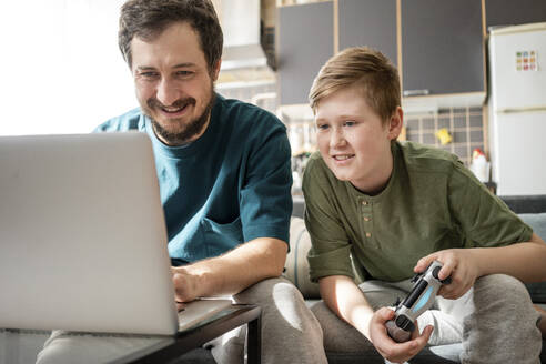 Portrait of father and son sitting together on the couch playing computer game - VPIF02306