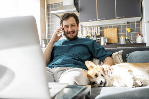 Portrait of smiling man on the phone sitting with dog on couch at home - VPIF02309