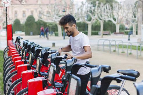 Young man taking a rental bike, Barcelona, Spain - XLGF00024