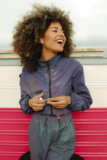 Portrait of happy stylish young woman wearing tracksuit outdoors - AGGF00034