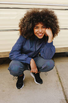 Portrait of happy stylish young woman wearing tracksuit outdoors - AGGF00037