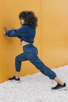 Stylish young woman doing stretching exercise at a yellow wall - AGGF00040