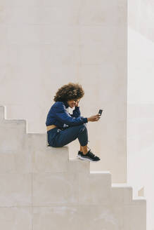 Stylish young woman wearing tracksuit and using cell phone on outdoor stairs - AGGF00043
