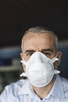 Mature man with protective mask looking at camera - MCVF00287
