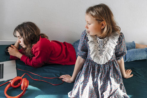 Two sisters with headphones and laptop resting on bed - OGF00267