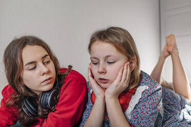 Portrait of two sisters with headphones lying together on bed - OGF00270