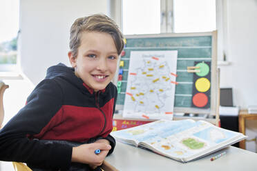 Portrait of smiling boy, learning at home - DIKF00437