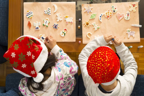 High Angle View Of Children Wearing Santa Hat Making Craft At Table - EYF04154