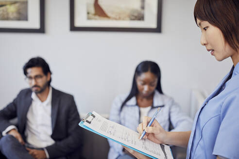 Receptionist checking form in waiting room of a dental practice - PWF00022