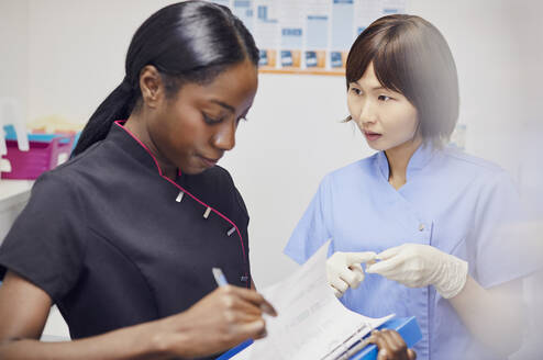 Dentist and denal assistant talking in practice - PWF00037