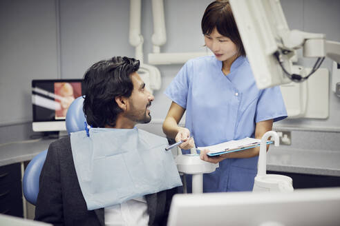 Medical secretary preparing dental treatment for patient - PWF00046