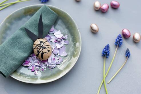Germany, Plate, cloth napkin, chocolate eggs, grape hyacinths and Easter bunny made of eggshell - GISF00573