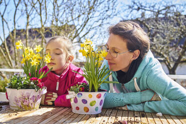 Mother and daughter smelling flowers  on balcony - DIKF00446