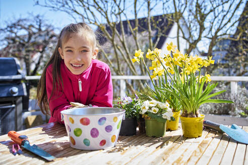 portrait of happy girl planting flowers  on balcony - DIKF00449
