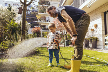 Father and son watering the lawn in garden - MFF05568