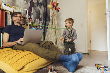 Son tying his father working on laptop in children's room - MFF05574