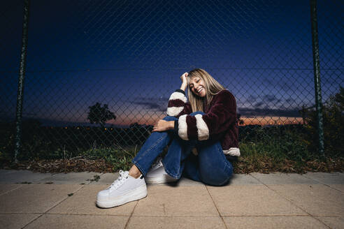 Young woman wearing fur jacket, sitting on the ground at night - MPPF00768