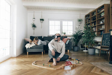 Father sitting in the middle of toys, using VR glasses, while son is lying on couch - KMKF01295