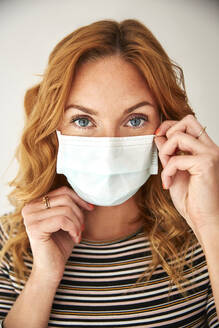 Portrait of red-haired woman wearing a protective mask at home - JHAF00074