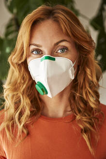 Portrait of red-haired woman wearing a FFP2 mask at home - JHAF00080