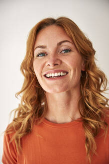 Portrait of smiling red-haired woman looking at camera - JHAF00083