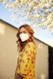 Portrait of red-haired woman wearing a FFP2 face mask in the city - JHAF00092