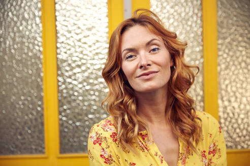 Portrait of red-haired happy woman in front of door, smiling at camera - JHAF00095