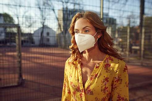 Portrait of red-haired woman wearing a FFP2 face mask in the city - JHAF00098