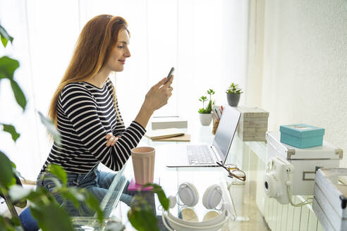 Young woman using smartphone at desk at home - AFVF05964