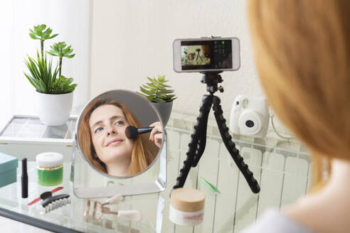 Young woman filming her beauty routine at home - AFVF05979