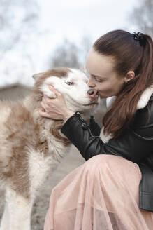 Woman kissing her husky - EYAF01024