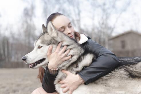Happy woman cuddling her dog - EYAF01027