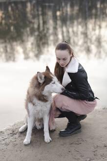 Woman crouching beside her husky at water's edge - EYAF01033
