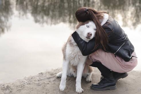 Woman hugging her husky at water's edge - EYAF01036