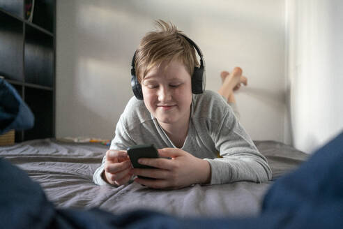 Portrait of smiling boy with headphones  lying on bed looking at cell phone - VPIF02332