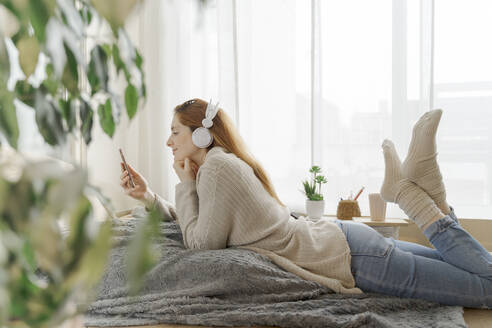 Young woman wearing headphones and using smartphone at home - AFVF06010