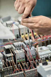 Close-up of electrician working on circuitry - ZEDF03202