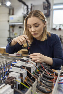 Female electrician working on circuitry in workshop - ZEDF03214